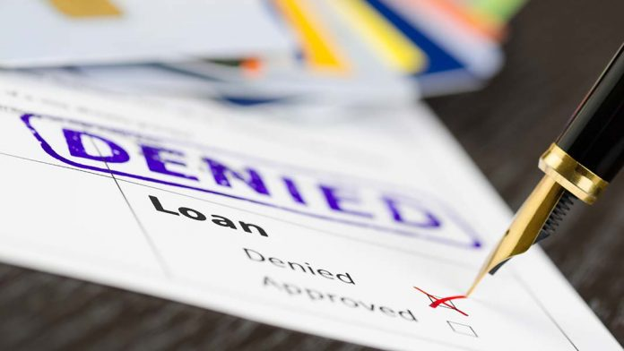 Pen ticking the denied box on a loan application